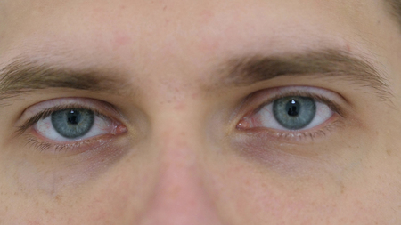 blinking eyes of young man close up at work in office stock photo