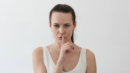Silence Please, Finger on Lips of Beautiful Young Woman, Portrait