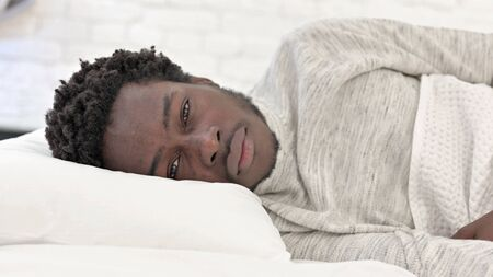Young African Man lying in Bed on Side