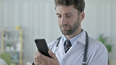 Cheerful Young Doctor using his Smartphone