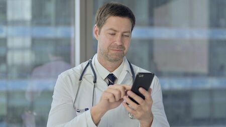 Middle Aged Doctor Using Smartphone, Scrolling