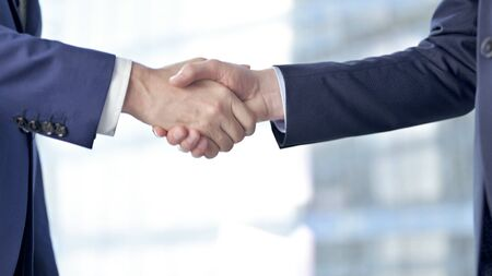 Close-up of Businessmen Shaking there Hands against Boardroom Window