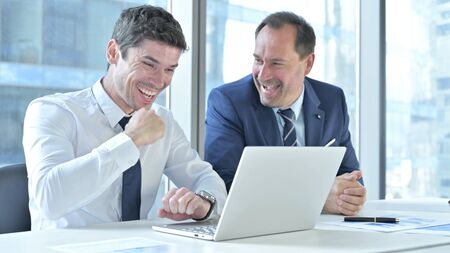 Businessmen Celebrating with both Fests while working on Laptop