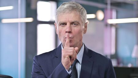 Portrait of Middle Aged Businessman putting Finger on Lips