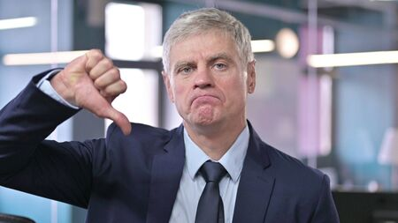 Portrait of Middle Aged Businessman showing Thumbs Down