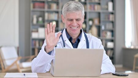 Cheerful Senior Doctor Doing Video Chat on Laptop while Sitting in Office