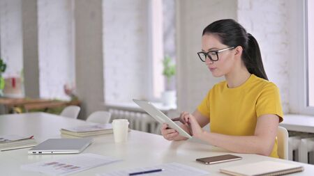Focused Young Female Designer working on Tablet in Modern Office