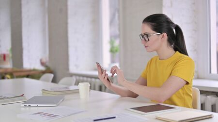 Young Female Designer Using Smartphone at Work