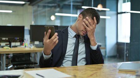 Sad African Businessman having Loss on Smartphone