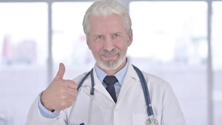 Portrait of Senior Old Doctor showing Thumbs Up