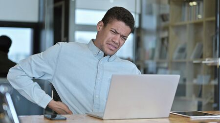 Tired Young African Man having Back Pain in Modern Office Standard-Bild