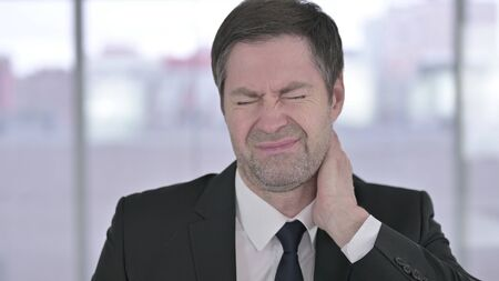 Portrait of Tired Middle Aged Businessman having Neck Pain