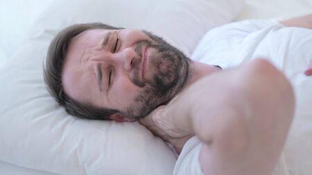 Sleeping Beard Young Man having Neck Pain in Bed 版權商用圖片