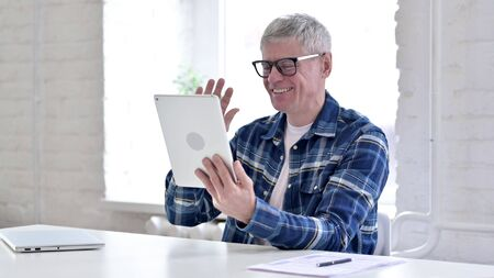 Casual Middle Aged Man Doing Video Chat on Tablet Stock Photo
