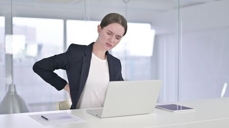 Tired Young Businesswoman having Back Pain in Office