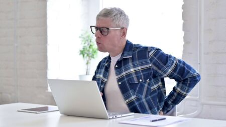 Tired Casual Middle Aged Man having Back Pain