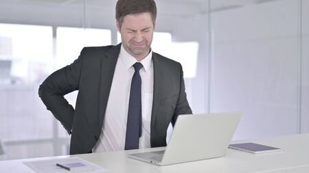 Tired Middle Aged Businessman having Back Pain