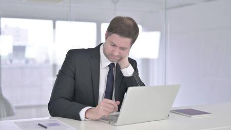 Hardworking Middle Aged Businessman having Neck Pain 版權商用圖片