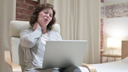 Old Woman having Neck Pain while Using Laptop on Chair