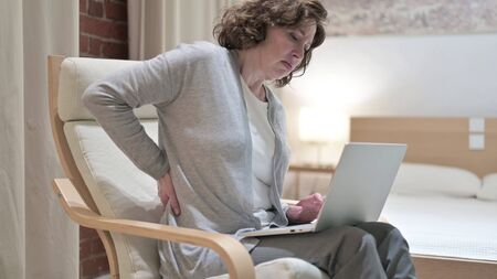 Exhausted Old Woman having Back Pain on Sofa