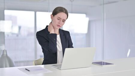 Hardworking Young Businesswoman having Neck Pain in Office