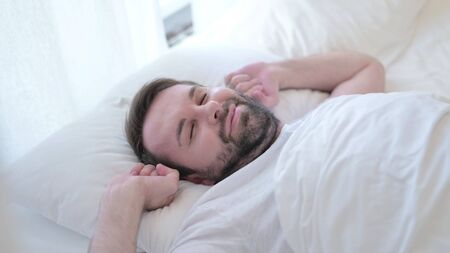 Attractive Beard Young Man Waking up and getting Out of Bed 版權商用圖片
