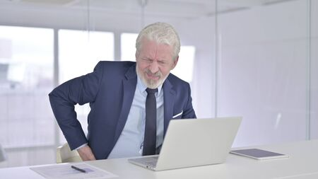 Tired Old Businessman having Back Pain