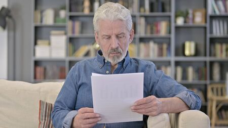 Old Man Reading Documents while sitting at Home Stock Photo