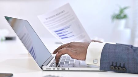 Close up of Hands of African Man doing Paperwork on Laptop