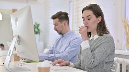 Creative Woman Working on Desktop and Coughing in Office