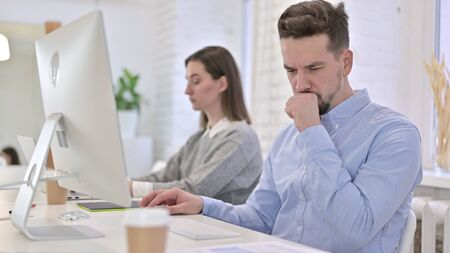 Creative Man Working on Desktop and Coughing in Office