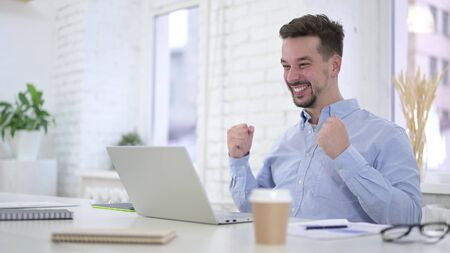 Excited Young Man Celebrating Success on Desktop