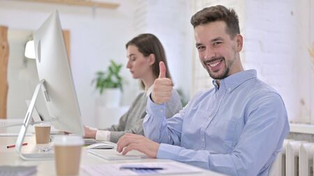 Ambitious Creative Man showing Thumbs Up in Office