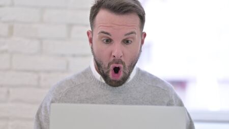 Wondering Shocked Man Reacting to Results on Laptop