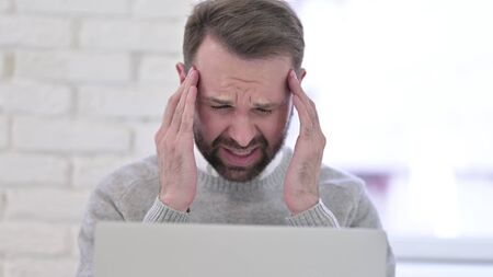 Close Up of Man with Headache at Work