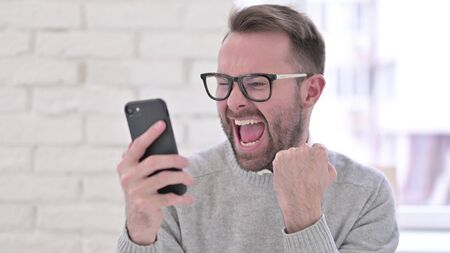 Creative Man Celebrating Success on Smartphone