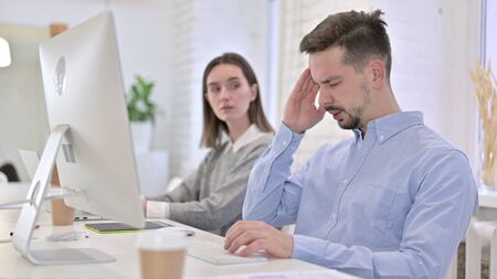 Tired Creative Male Professional having Headache in Office