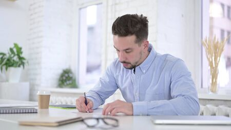 Creative Young Man Writing on Paper at Work, Paperwork