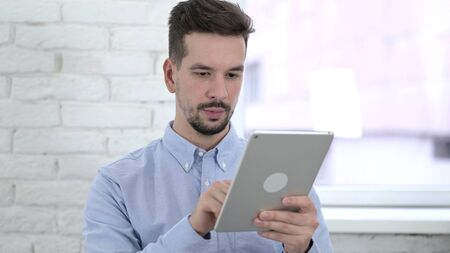Young Man Using Tablet in Modern Office