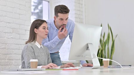 Creative Man Discussing Work with Woman working on Desktop