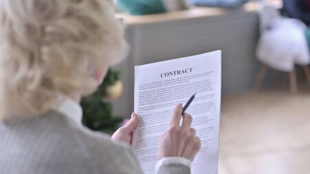Rear View of Focused Old Woman Reading Contract