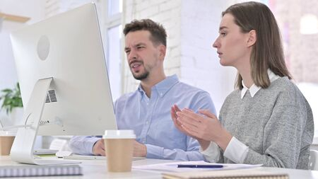 Shocked Creative Team Reacting to Failure on Desktop in Office