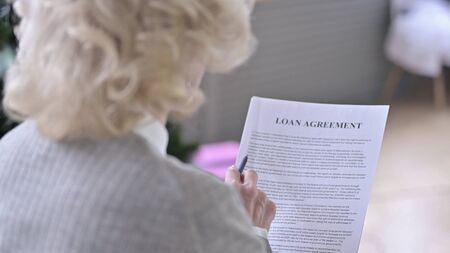 Rear View of Old Woman Reading Loan Agreement
