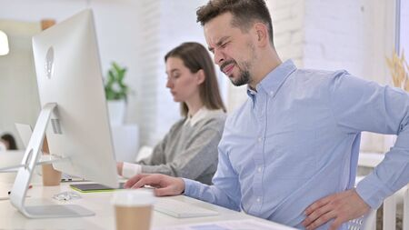 Tired Creative Man having Back Pain in Modern Office