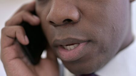 Close up of African Man Talking on Smartphone in Office Archivio Fotografico