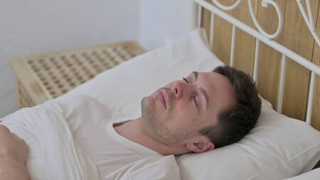 Attractive Young Man Sleeping in Bed Peacefully Imagens
