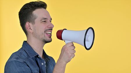 Young Man making Announcement on Loudspeaker, Yellow Background Reklamní fotografie
