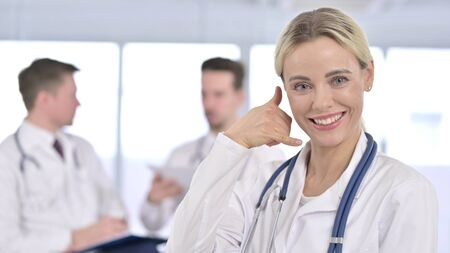 Beautiful Female Doctor showing Call Me Sign with Hand Imagens