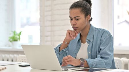 Pensive Young African Woman working on Laptop
