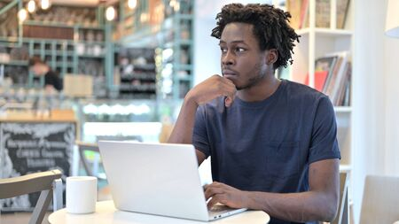 Pensive African Man Working on Laptop in Cafe Archivio Fotografico